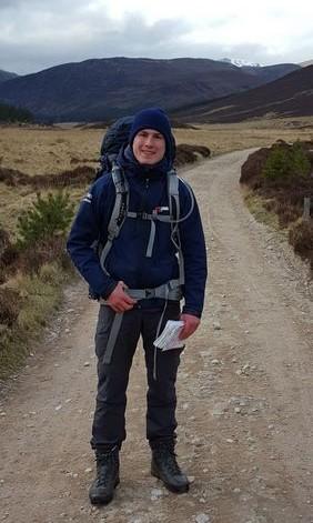 Joost Branderhorst staat in wandelkleding met rugzak op een zandpad met uitzicht op bergen