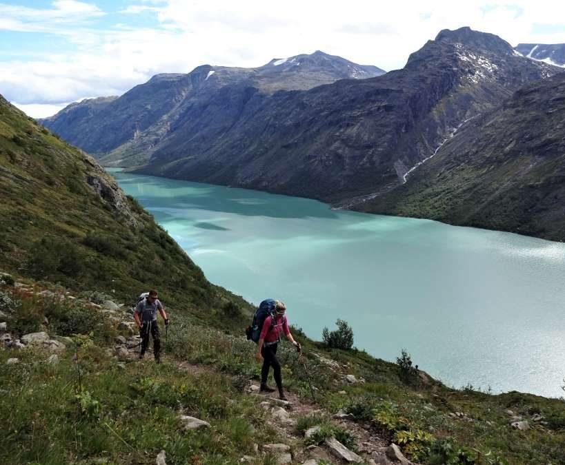 Twee trekkingcursisten met rugzak wandelen langs blauw groen meer en bergen in Noorwegen