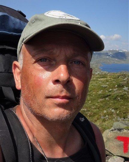 Tom Verrillo wildernisgids een selfie met uitzicht op het landschap van Noorwegen.