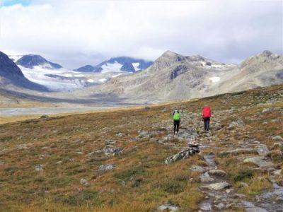 Rugzaktrektocht met Northern Pioneers wildernistrekkings door het ruige bruin groene landschap met besneeuwde bergen in Noorwegen