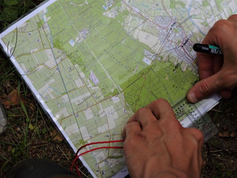 Cursist maakt met kaarthoekmeter en stift aantekeningen op een landkaart voor een routebepaling