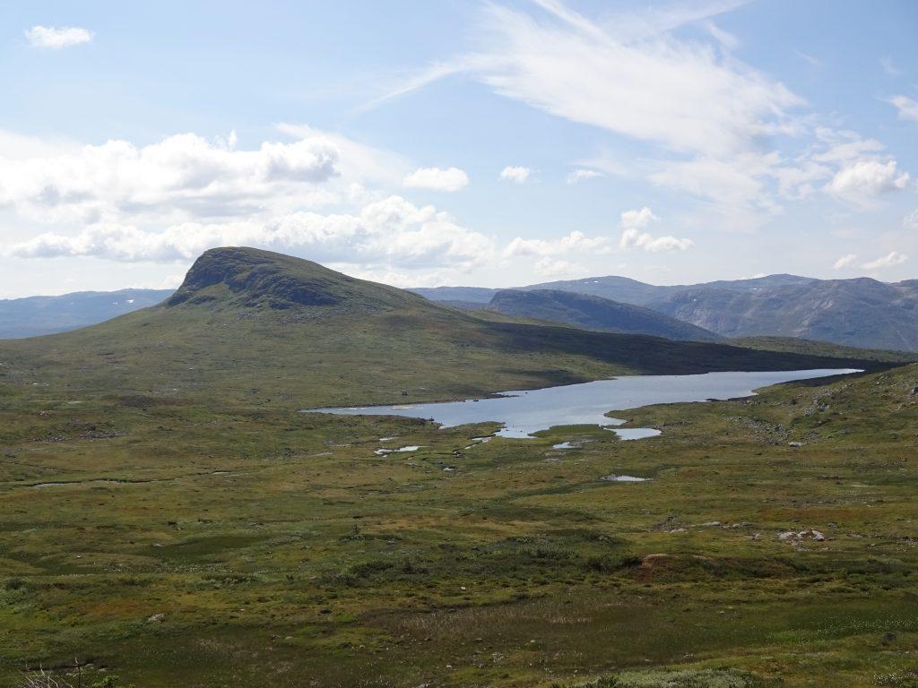 Verlaten kaal ruig berglandschap met meer met een helder blauw bewolkte lucht in Noorwegen Setesdal tijdens een rugszaktrekking van Northern Pioneers.