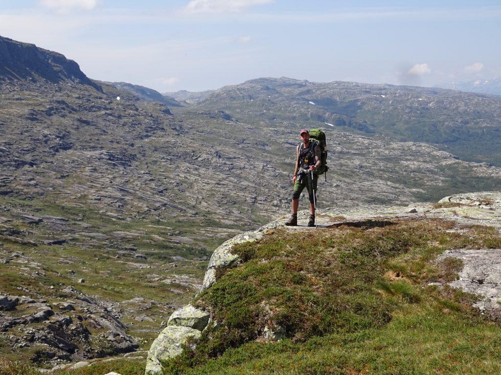 Cursist rugzaktrekking en navigatie staat in een verlaten berglandschap boven op een grote rotspartij in Noorwegen.