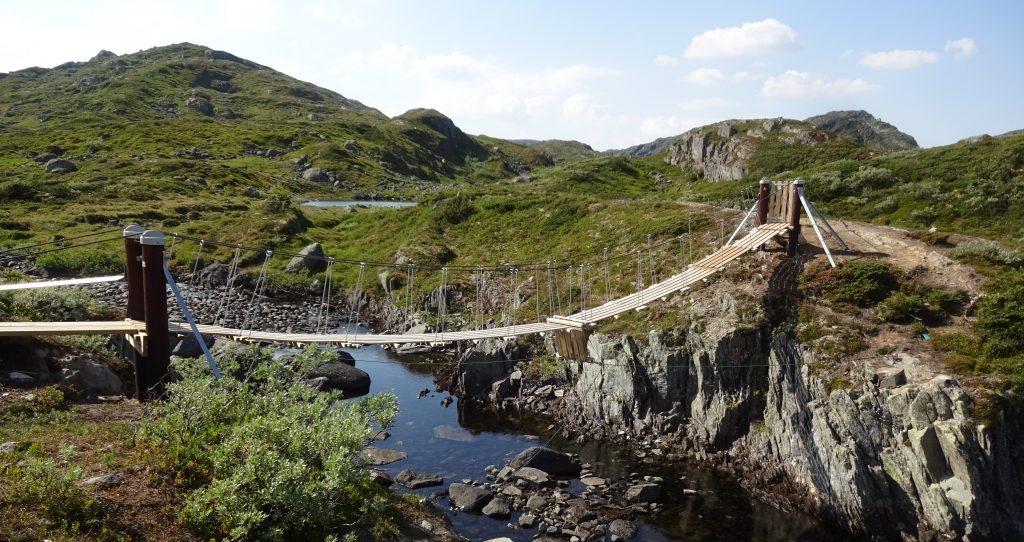 Houten hangbrug over klein riviertje in bergachtig gebied Setesdal Noorwegen.