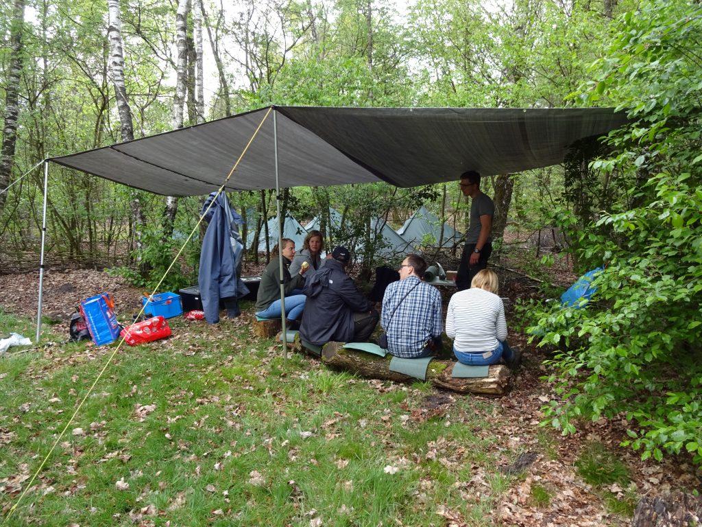 Cursisten zitten in het bos op houten boomstammen onder een tarp met daarachter alle opgezette tarps voor de overnachting.