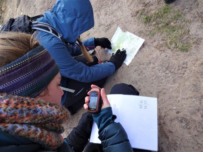 Twee cursisten in winterkleding zitten in het bos op de knieen met een kaart en kompas en papier en pen in de handen hun route te bepalen.