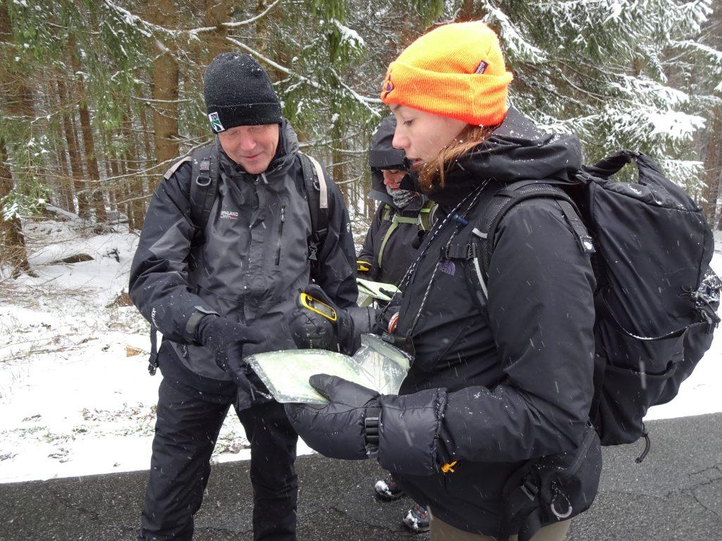Drie cursisten in winterkleding en rugzak op, gaan op pad met kaart, kompas en gsp in de besneeuwde bossen van het Harzgebergte Duitsland tijdens hun cursus navigatie.