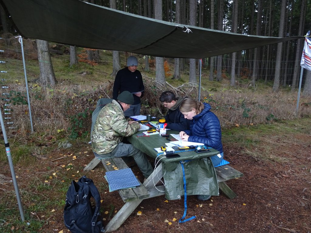 De wildernisgids van Northern Pioneers geeft aan een picknicktafel en onder een tarp les in kaart, kompas en gps aan cursisten tijdens het navigatieweekend in de Harz Duitsland.