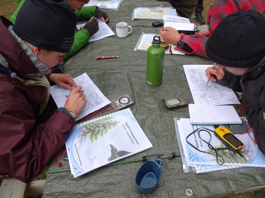 Cursisten zitten aan een houten picknick tafel voor les in navigatie met kaart kompas en gps.