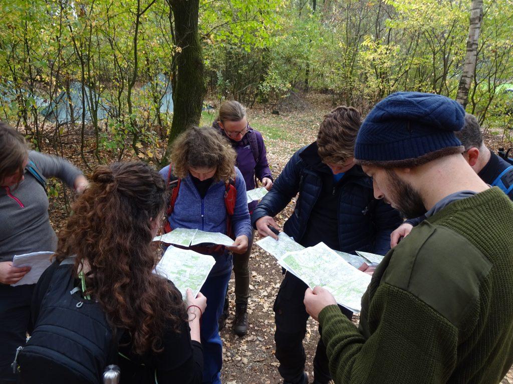 Cursisten staan in het bos in Twente in een groepje bij elkaar op de landkaart te kijken waar ze naartoe moeten.