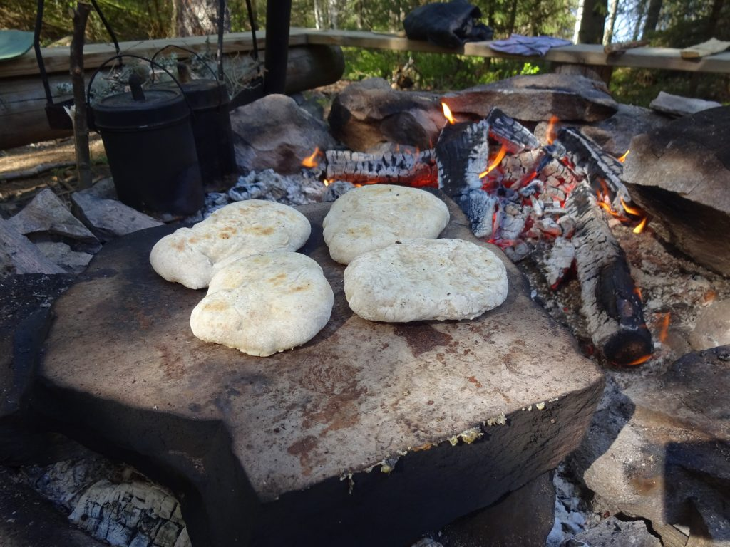 Een heet rotsblok in het kampvuur met daarop een aantal broodjes die worden gebakken.