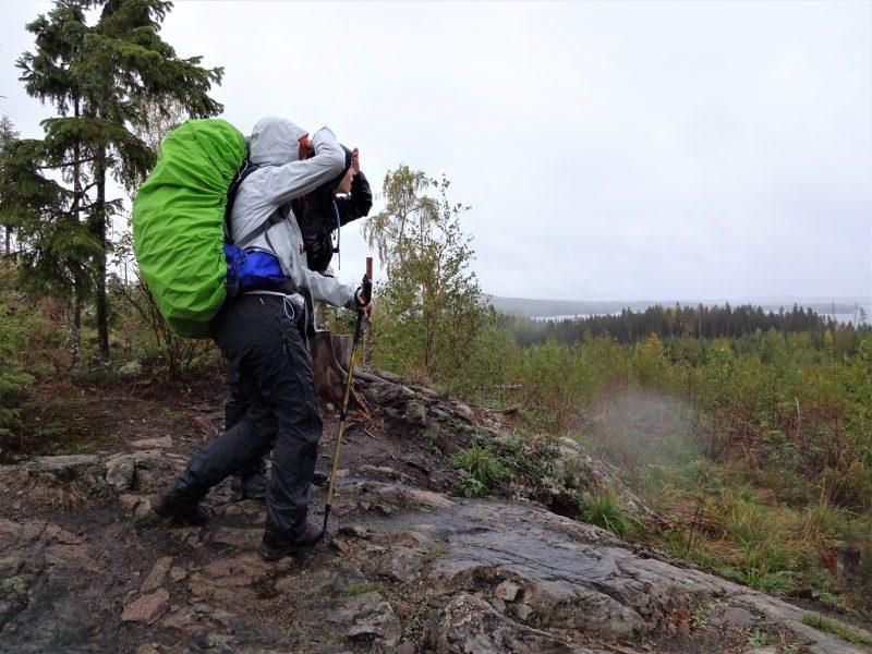 Twee cursisten van Northern Pioneers staan met rugzak en wandelstokken boven op rotsen te kijken naar het dal met dennenbomen en een meer in de verte.