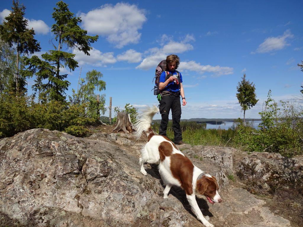 Cursist loopt met hond over een rots met achter haar uitzicht op een meer en een blauwe licht bewolkte lucht in Zweden.