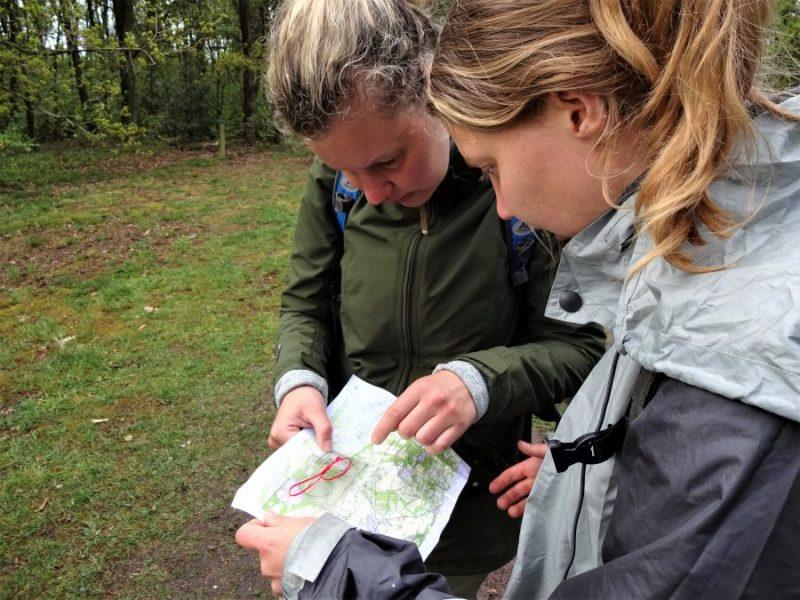 Twee cursisten van Northern Pioneers staan in de bossen van Vasse Twente samen op een landkaart te kijken met een kaarthoekmeter erbij.