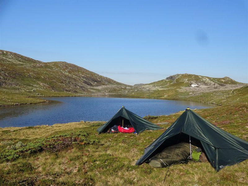 Twee tarps staan als tent opgesteld in een kaal Noors landschap aan een meer met daarachter bergen.
