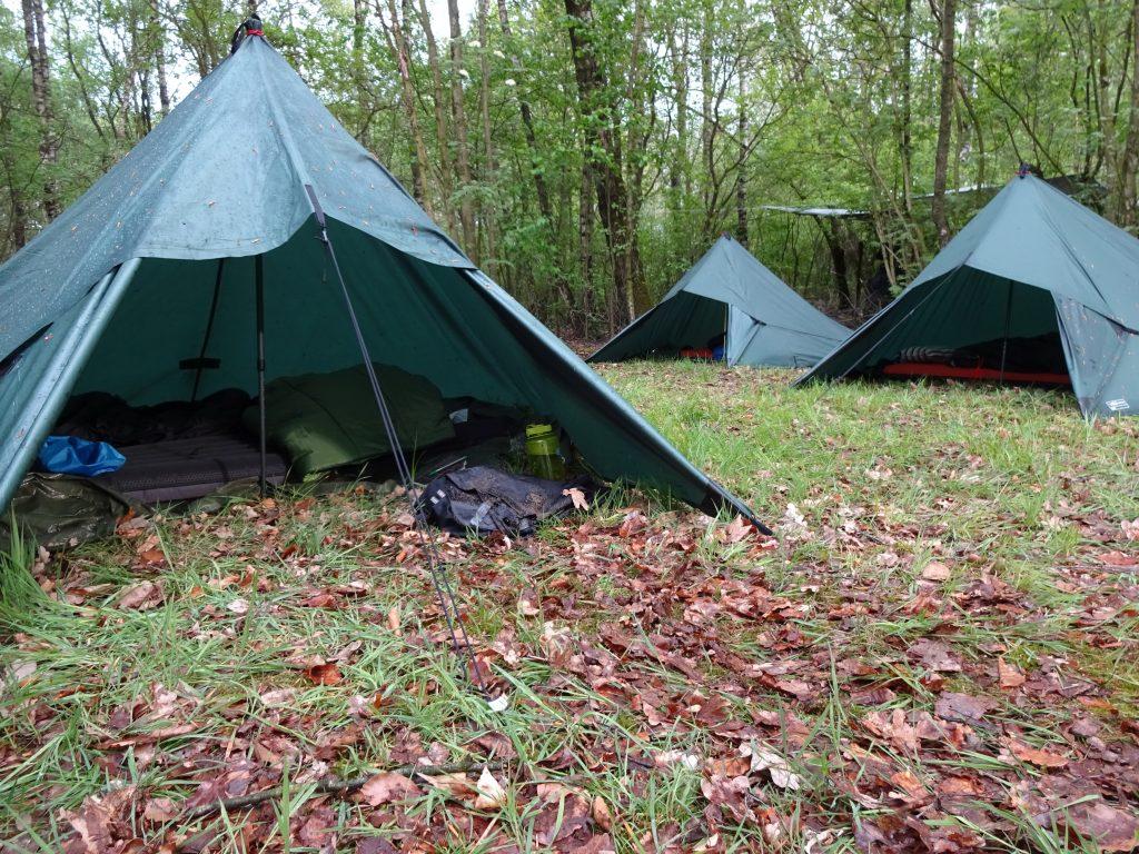 Drie groene tarps staan als open tent opgesteld voor overnachting in de bossen in Twente.