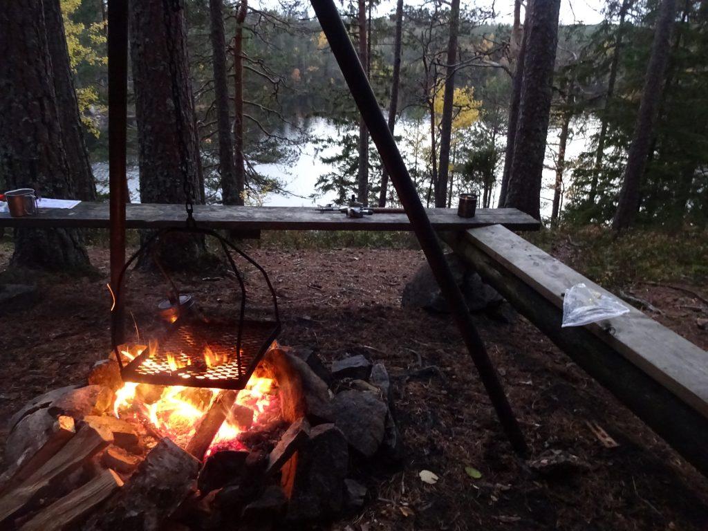 Nachtelijk kampvuur bij een shelter met rondom zit planken met tussen de bomen door uitzicht op een meer.