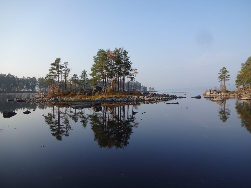 Sfeerfoto van een klein Zweeds eilandje met rotsen en bomen met weerspiegeling in het meer.