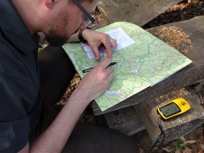 Cursist zit op een bank van de picknicktafel en meet met een kaarthoekmeter de route op een landkaart en naast hem ligt een gps.