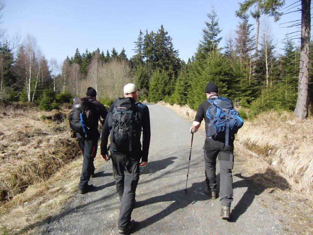 Drie cursisten met rugzak wandelen heuvelopwaarts in het Harzgebergte tijdens hun navigatiecursus.