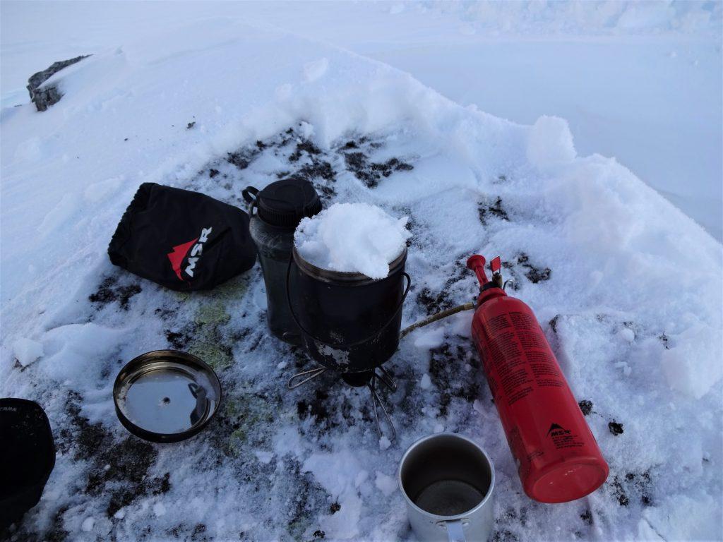 Op een rotssteen in een wit besneeuwd landschap staat een gasbrander met een billycan erop gevuld met sneeuw met daarnaast een aluminium beker.