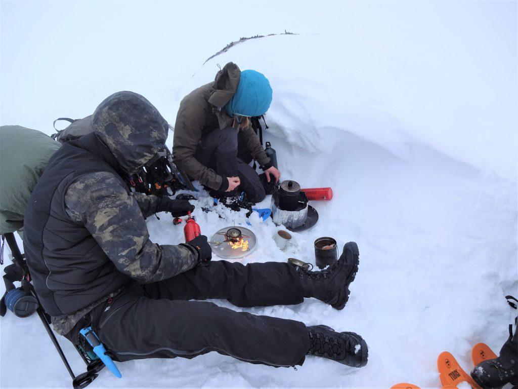 Cursisten zijn zitten in de sneeuw met hun kookset en maken hun eten klaar tijdens een rugzaktrekking in Noorwegen.