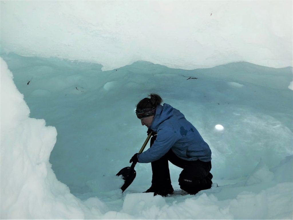 Cursist is bezig met het uitgraven van een quinzee ook wel sneeuwhut genoemd.