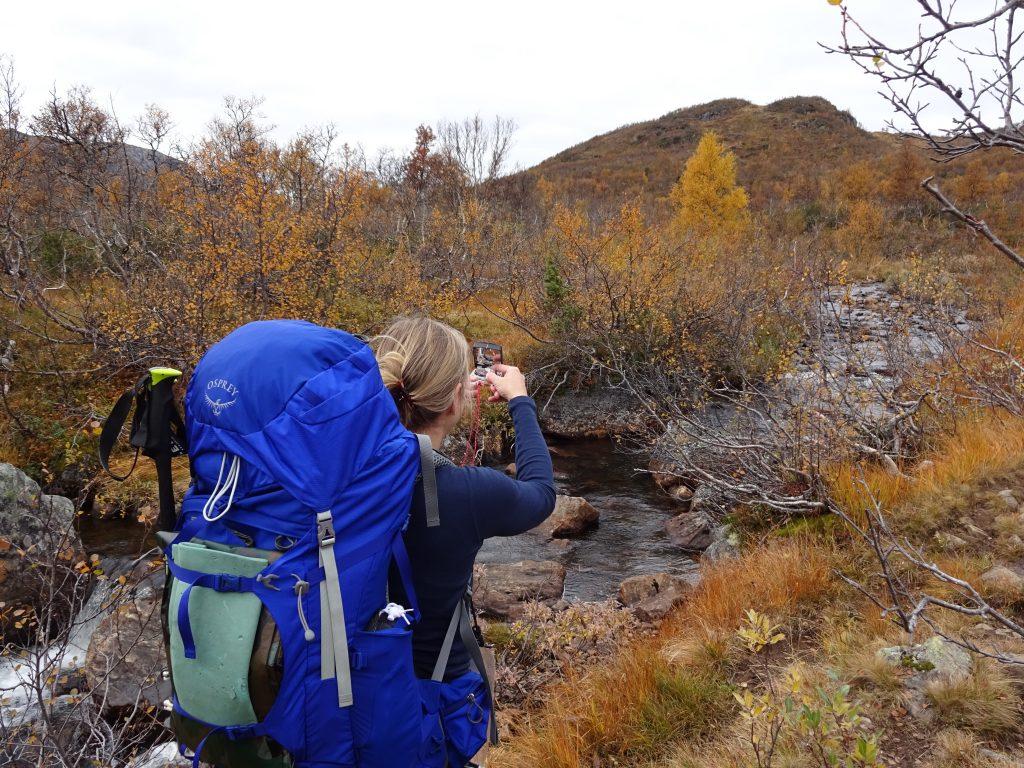 Cursist met rugzak staat met kompas een peilmeting te doen in een berggebied in Noorwegen in de herfst.