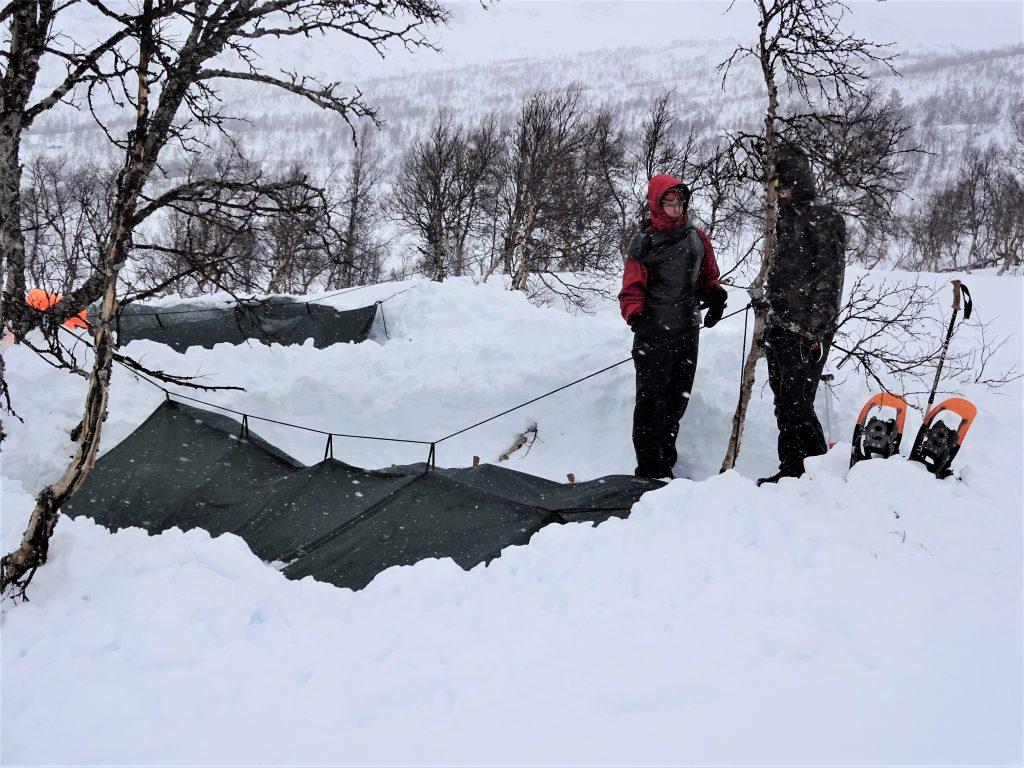 Cursisten staan in winterkleding in besneeuwd berggebied in Noorwegen en hebben een shelter voor het winterkamperen opgezet.