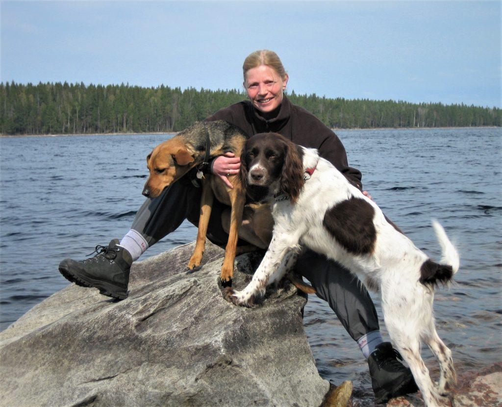 Vrouw zit in outdoorkleding op rots met twee honden in haar armen met achter haar een groot meer en een rand dennenbos in Zweden tijdens een trektocht.