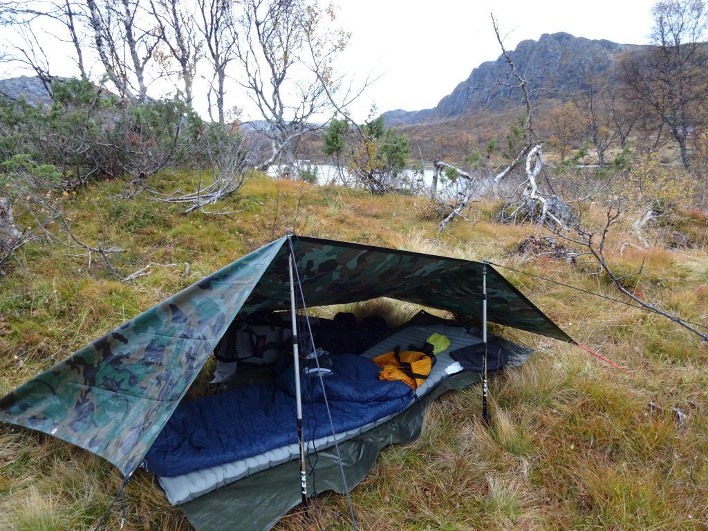 Na een dag hiken door het berggebied in Noorwegen wordt de tarp opgezet met hierin de slaapspullen en rugzak met op de achtergrond een meer en bergen.