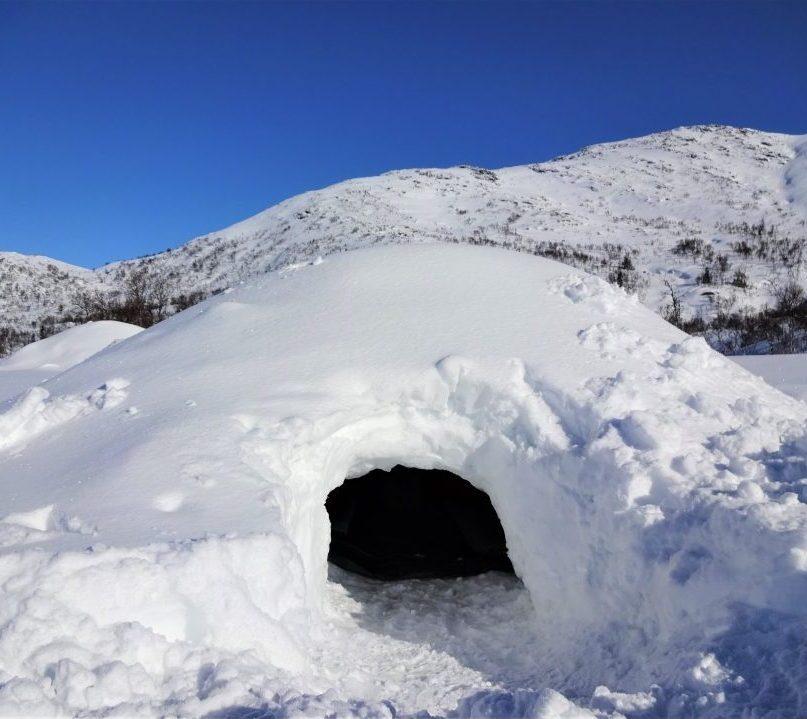 Zelf gebouwde sneeuwhut/quinzee met bergen op de achtergrond in het sneeuwlandschap van Noorwegen.