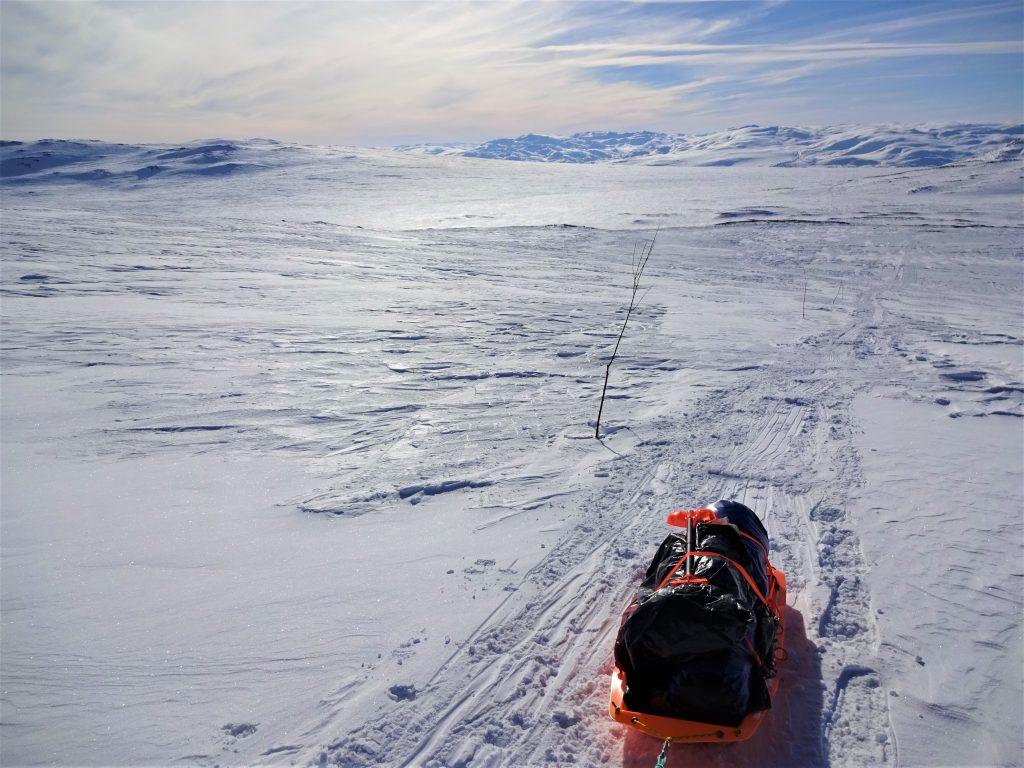 Wit sneeuwlandschap met bergen op de achtergrond en een blauwe lucht met op de voorgrond een oranje beladen expeditieslede van Northern Pioneers.