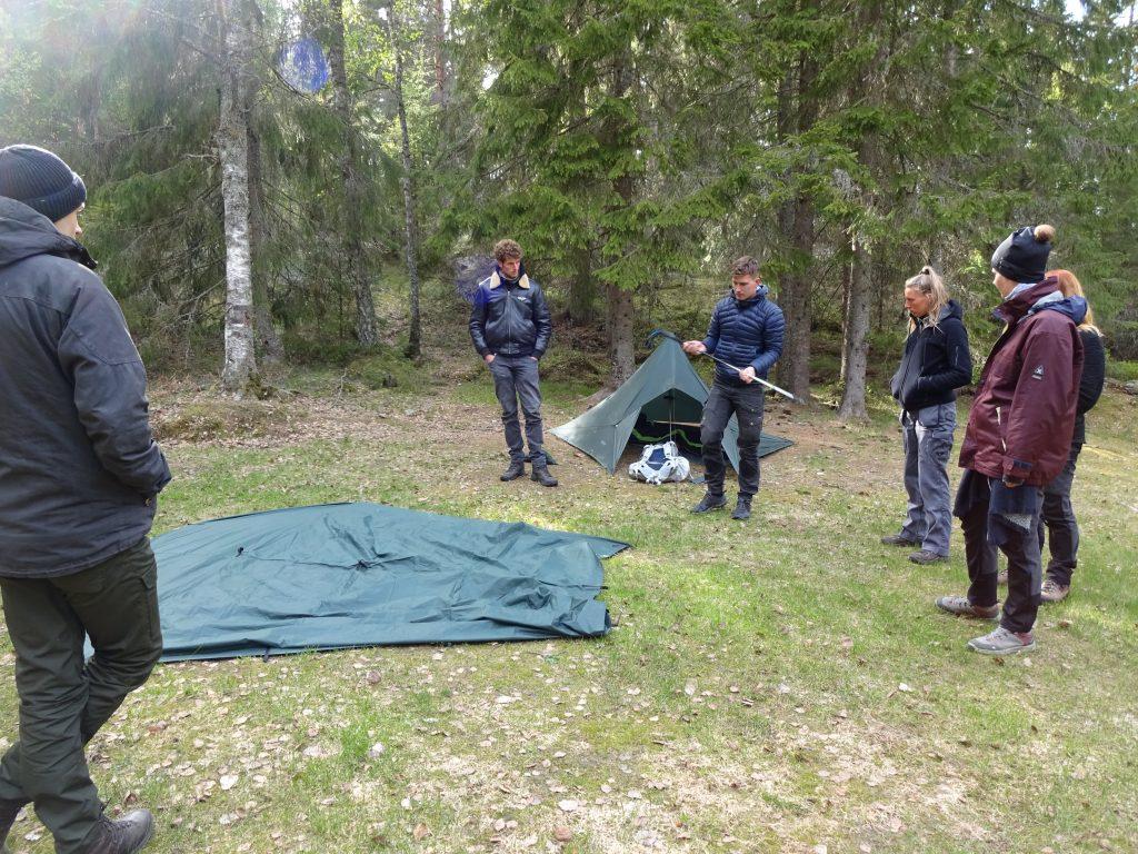 Cursisten krijgen les van stagiair hoe ze een tarp moeten opzetten in een natuurgebied in Zweden.