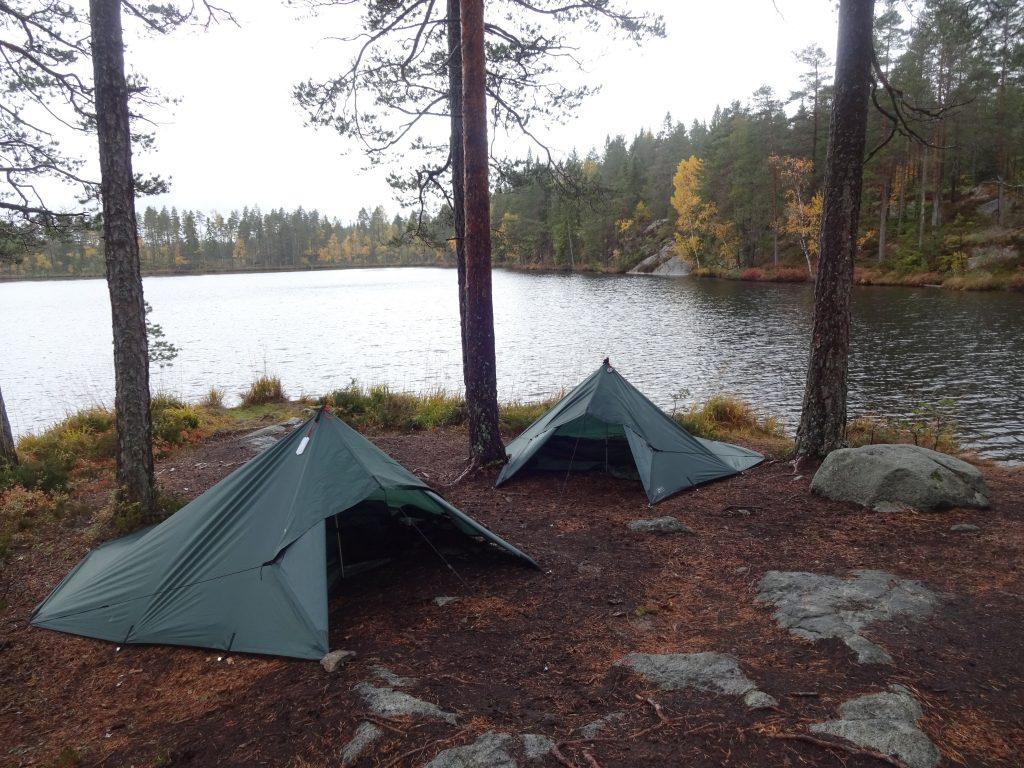 Groene tarps staan tussen een paar bomen aan de rand van een Zweeds meer met aan de overkant het bos in herfstkleuren.