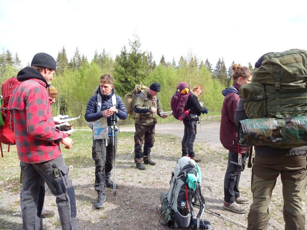 Groep cursisten trekkingschool staan met rugzak op te navigeren met kaart, kompas en gps om op hun kampeerplek te komen.