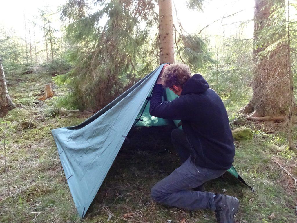 Cursist zet tarp op tussen de dennenbomen bij het basiskamp van de trekkingschool.