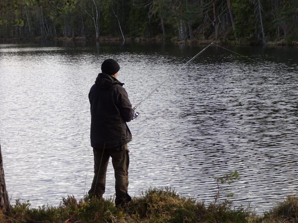 Cursist staat te vissen aan een meer in Zweden tijdens de survivaltrektocht.