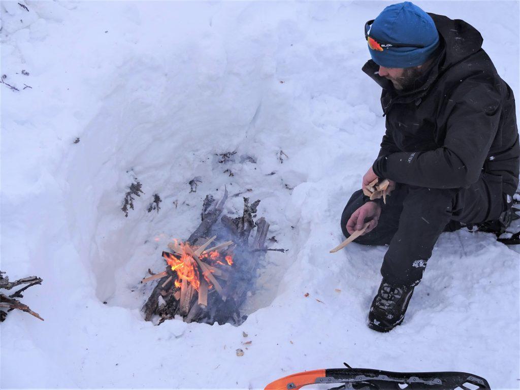 Cursist zit bij het kampvuur dat hij heeft gemaakt in een kuil in de sneeuw tijdens wintertrekking in Noorwegen.