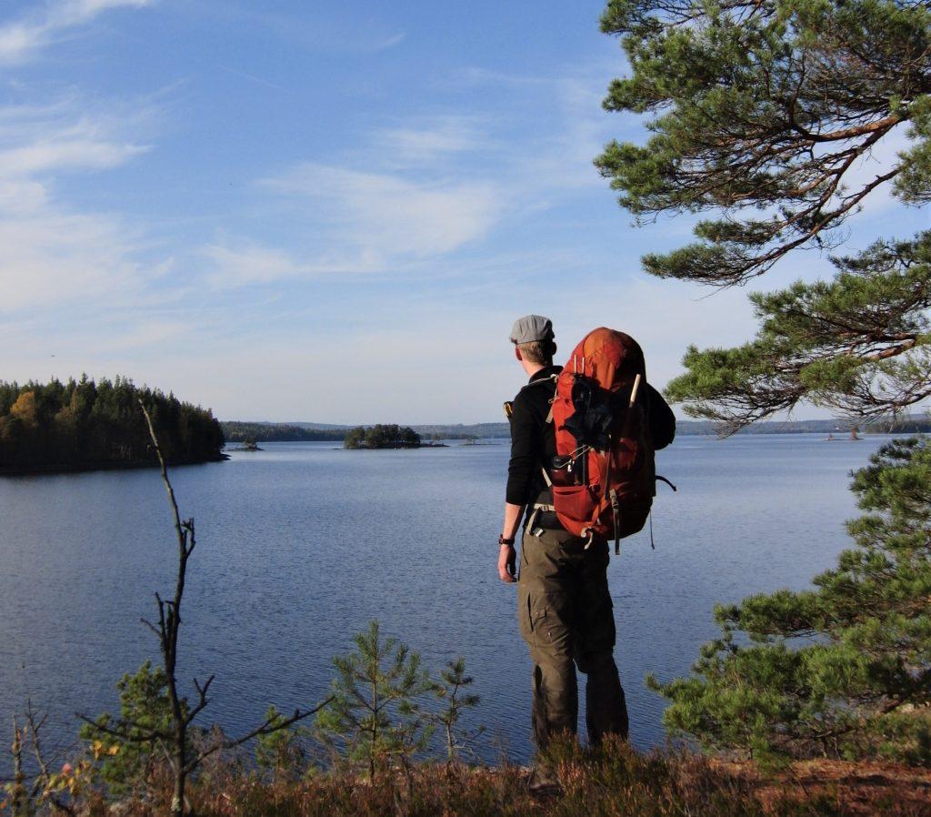Cursist staat met rugzak aan de rand van een groot meer in Zweden in de verte te kijken met uitzicht op kleine met dennen begroeide eilandjes en een stralend blauwe lucht met enkele wolkvegen.