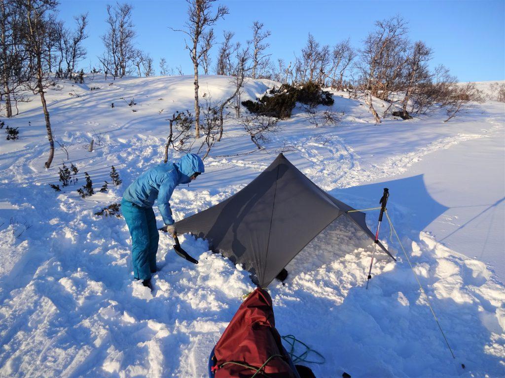 Cursist zet een tarp neer in de sneeuw en schept sneeuw langs de rand van het doek om de wind buiten te houden in Noorwegen.