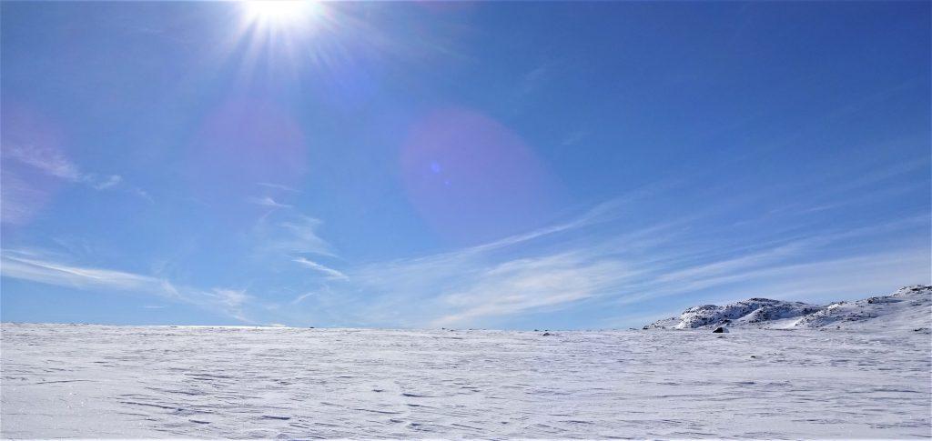 Een helder sneeuwlandschap met helder blauwe lucht en stralende zon tijdens een rugzaktrektocht in Noorwegen.