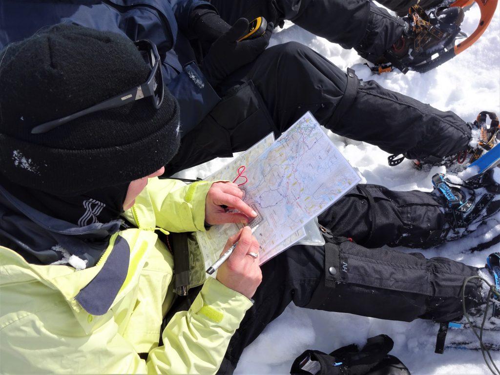 Cursisten zitten in de sneeuw en bepalen op de landkaart met een kaarthoekmeter de route tijdens het navigeren bij de rugzaktrektocht in Noorwegen.