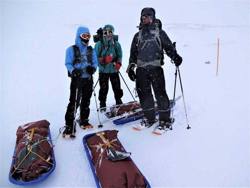 Cursisten staan in winterkleding en met pulka's te poseren in het besneeuwde winterse berglandschap van Noorwegen.