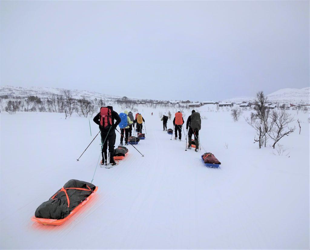 Groep cursisten loopt op sneeuwschoenen en een slede achter zich aal door het besneeuwde Noorse landschap vanwege een wintertrekking met Northern Pioneers.