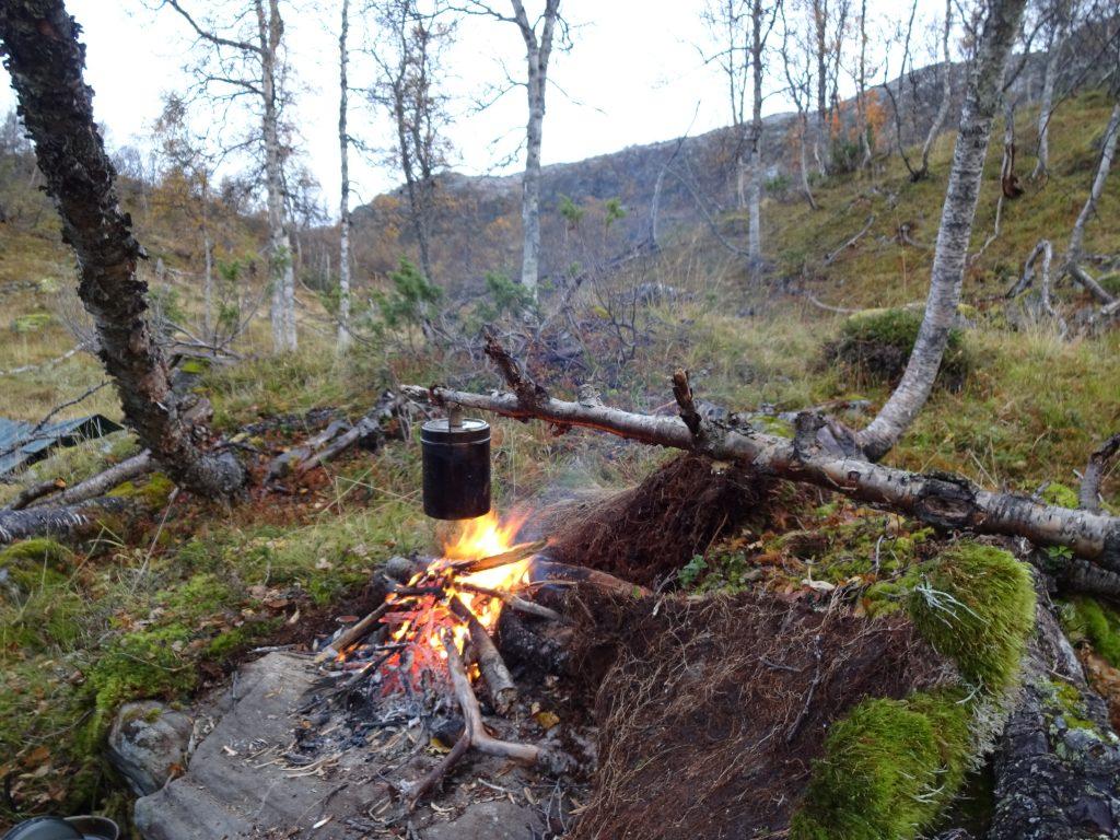 Een billycan hang aan het uiteinde van een boomstam boven het kampvuur in berggebied in Noorwegen tijdens een survival week.