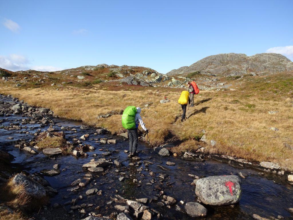 Drie cursisten van de trekkingschool steken een rivier over middels stenen in de rivier met uitzicht op bergen in Noorwegen.
