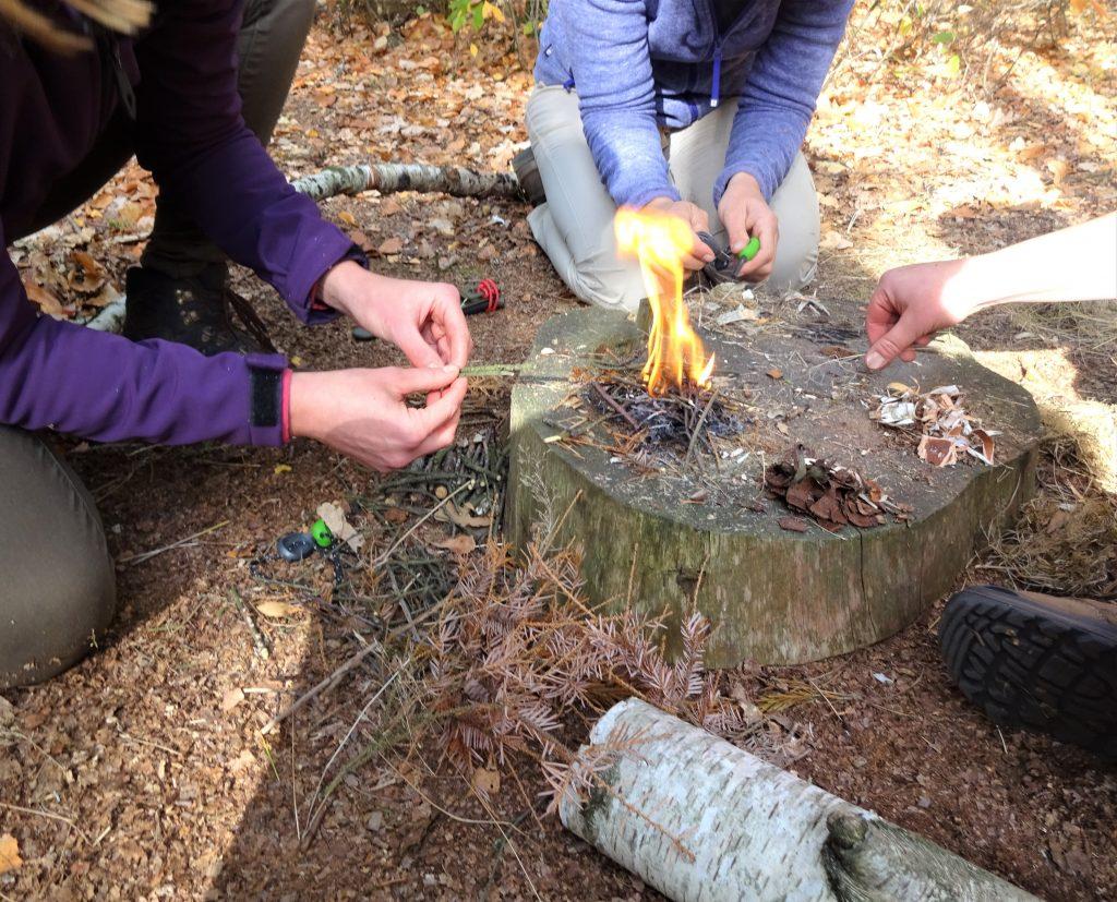 Op een houtblok in een bos maken cursisten een vuurtje aan met een firestriker.