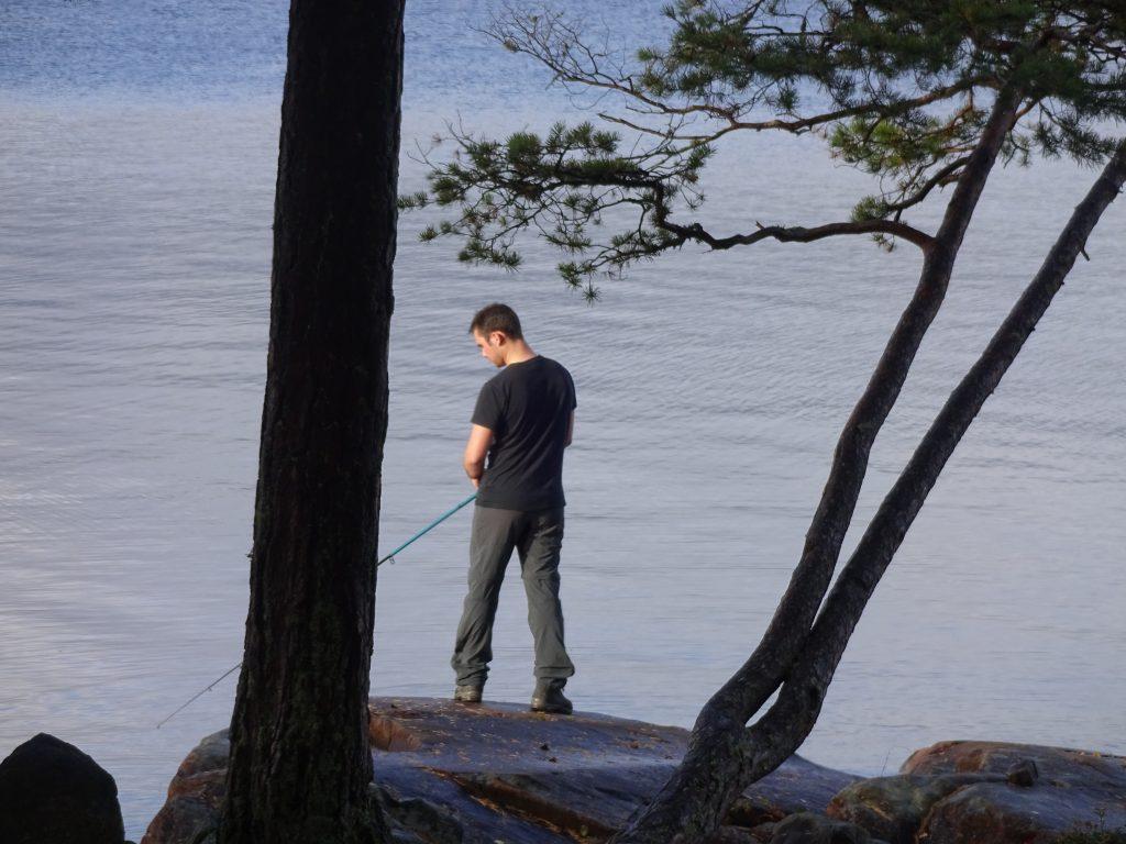 Mannelijke cursist staat op een rots te vissen in een meer in Zweden.