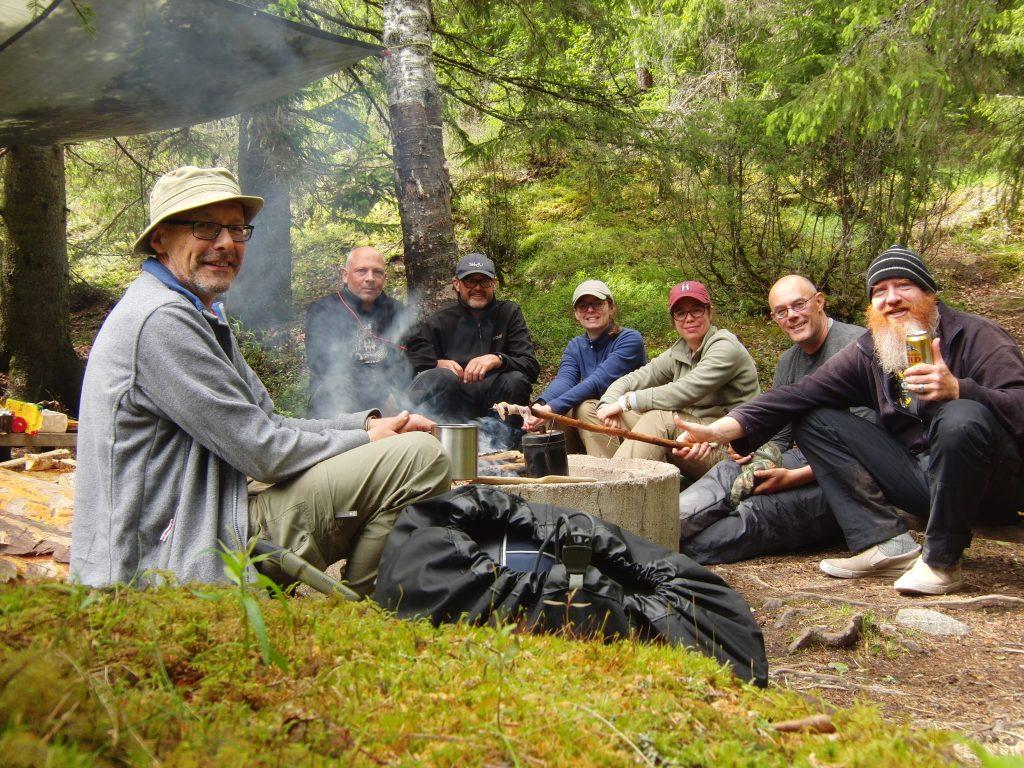 Gids zit samen met cursisten rondom kampvuur waarbij water wordt gekookt in een billycan en wordt gedronken.